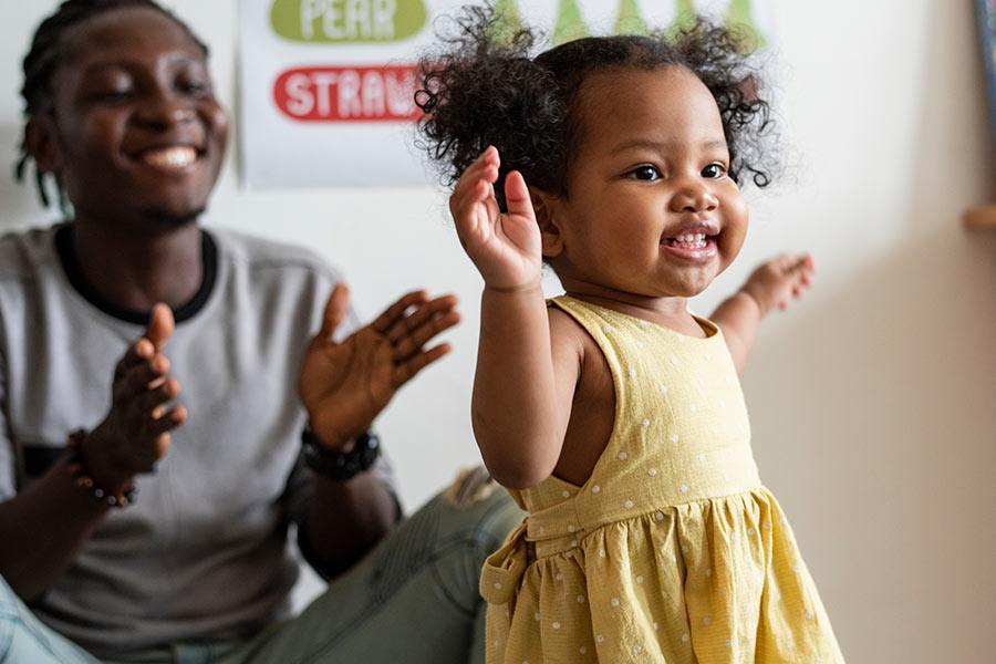 man clapping to dancing toddler