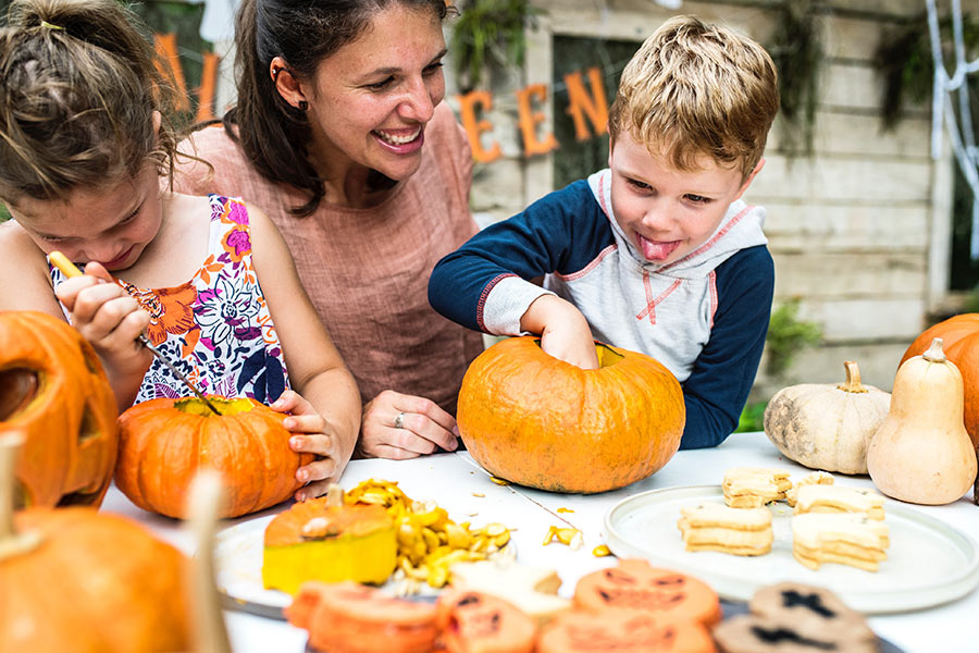 woman and two children carving pumpkins