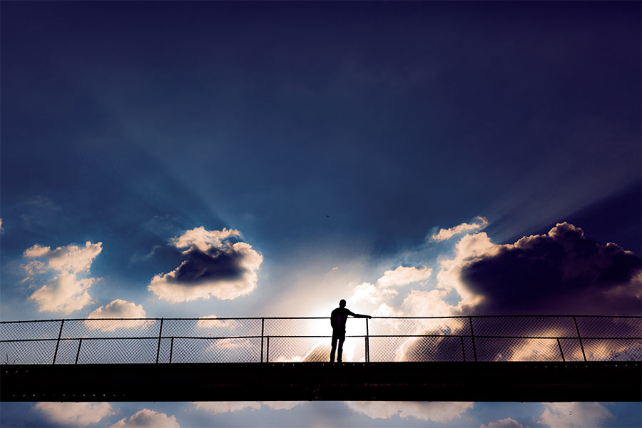 man stading on bridge in front of sunlit clouds