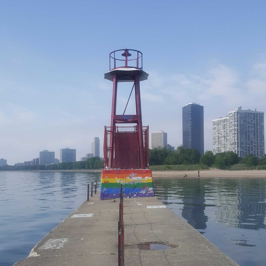 Beacon on the Chicago lakefront painted with a rainbow flag.