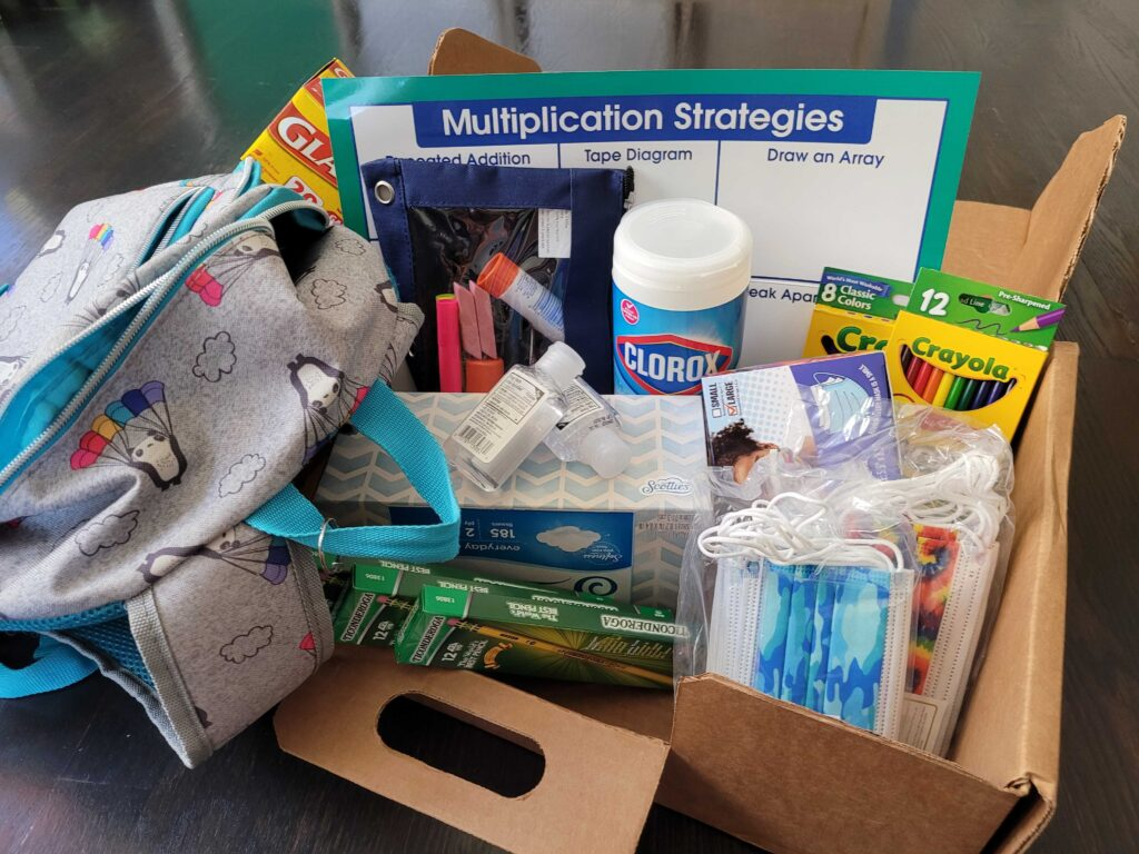 A collection of school supplies, including a backpack, pencils, tissues, face masks, art supplies, cleaning wipes and a backpack.