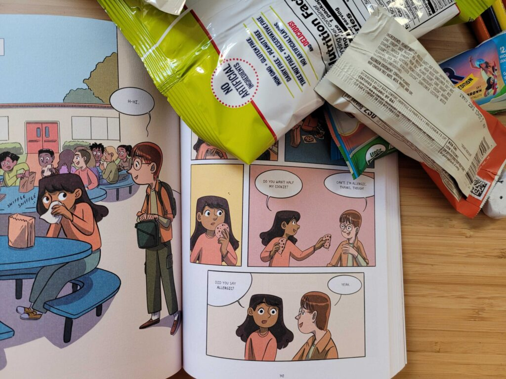 Image shows a graphic novel open to page where a student tries to share a cookie, but the offer is declined due to an allergy. Also in the image are school snacks with listed allergens.