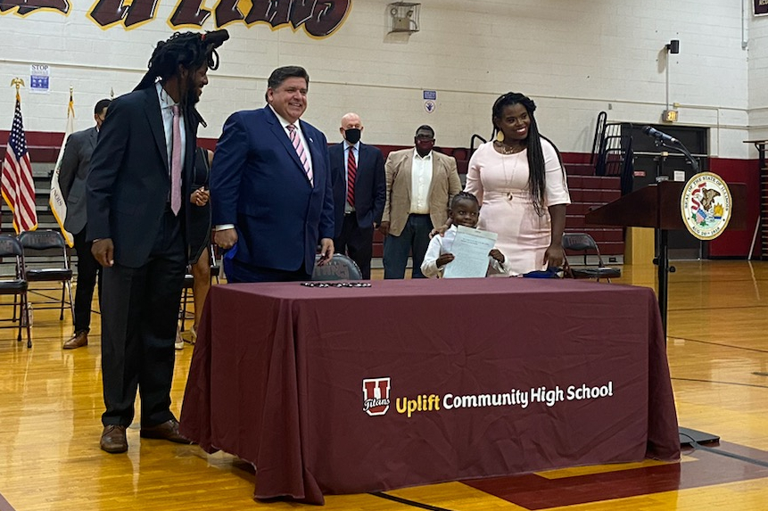 Image shows Senator Mike Simmons standing next to Governor JB Pritzker, Jett Hawkins, and Ida Nelson after the legislation was signed.